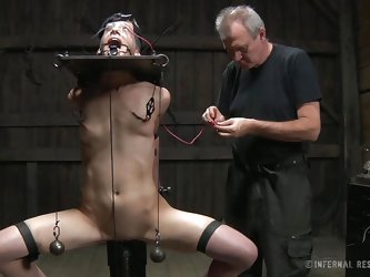 Elise tries to scream for help, but the word can't be made out because of the clamps around her mouth and tongue. He master turns up the power on