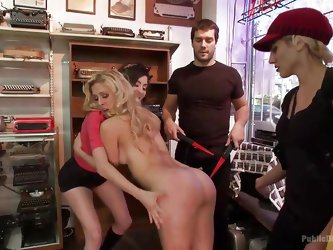 Cherie Deville is marched into a store to be publicly humiliated by a group of men and mistresses. One of the dommes wraps her strong arms around her