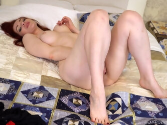 Desirable redhead Alice Wonderland pleasures her pussy on the bed