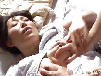 This mature Japanese beauty wakes up horny, and she wants some morning sex with her husband. He tears open her blouse and sucks her nipples before mov