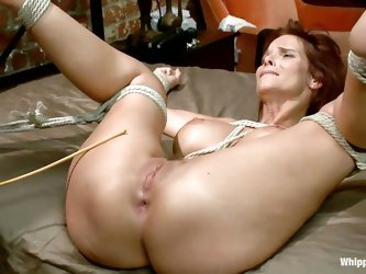 Tied on the bed with her legs spread the milf is being spanked by a young redhead chick. The beautiful girl is mad about her because she said they wil