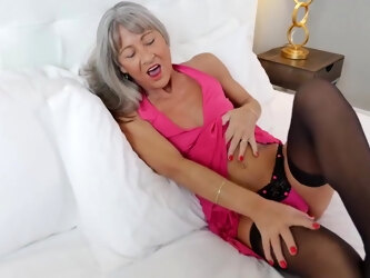 Mature blonde in black stockings and pink dress is toying her perfectly shaved pussy like crazy