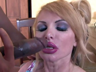 Taylor Wane is a mature blonde wife who gets down on her knees to suck big black dick of tall skinny guy in front of her hubby. Chocolate guy stands s
