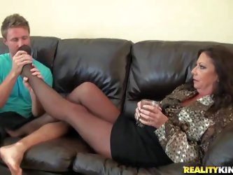 Dark haired and really hot milf in jacket and short skirt enjoys in getting a hot foot massage from her hot young blonde neighbour on the couch and ge