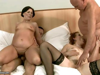 Margo T and Eodit are two horny grannies that get their mouths and dripping wet pussies fucked side by side. Two fuck hungry oldies do it on a king si