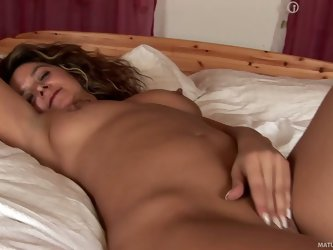Alluring milf Emanuelle is finally in her bed after night out. She is naked and enjoys relaxing masturbation session. She rubs her juicy mature pussy