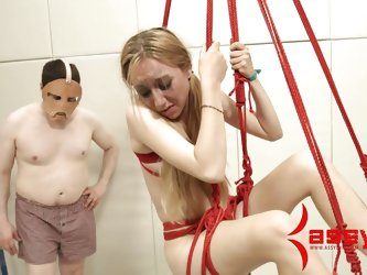She has a cock slapped against her face and the make up is running down her chin. The slave is elevated above the ground in rope bondage so that her f
