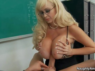 Brittany O'Neil is a gorgeous blond haired MILF teacher with gigantic breasts. She pulls out her jugs in front of hard dicked student. She gives