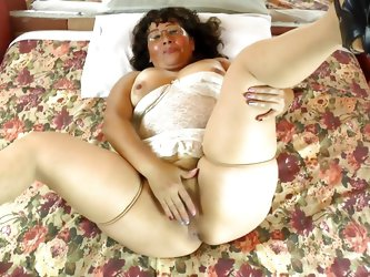 Dirty bitch Maribel lays on the bed with her tits hanging out of her corset. She lifts up her fat rolls and grabs at her hairy pussy. She is getting v