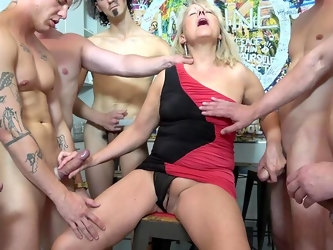 Hot mature surrounded by dicks and made to swallow a lot