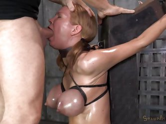 This dirty slut is tied up to the stocks with rope. The rope is wrapped very tight around her big boobs which makes them bulge out and start to turn p