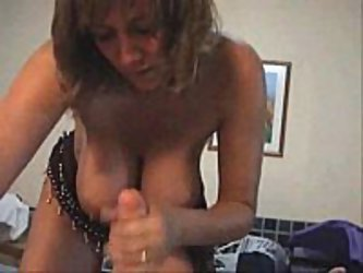 A mature blonde with huge tits  rubs on her man's member as her massive boobs hang low over him.  She jerks him nice and hard before he explodes