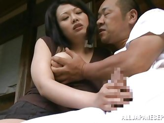 After doing laundry, this couple is out in the cabin sitting on the porch in the Japanese woods. She pulls his cock out and gives it a nice tug. Watch